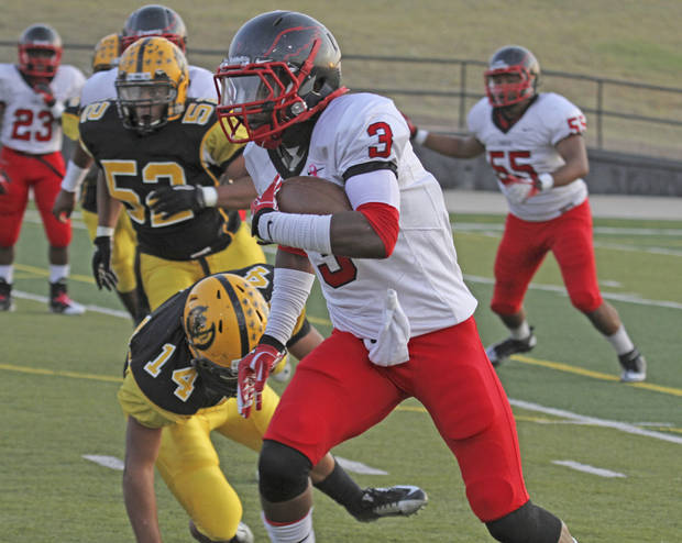 Del City&#039;s Corey Lawrence, right, carries the ball as Lawton MacArthur&#039;s Miguel Rosario defends during a Sept. 20, 2012 game in Lawton. PHOTO BY BRANDON NERIS, THE LAWTON CONSTITUTION