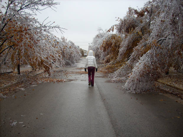 WINTER / COLD /  WEATHER: Taylor Clark walks down her street Monday in the Rivendell addition in Oklahoma City. A series of ice storms weighed down trees along many metro roadways. ORG XMIT: 0712102137181372