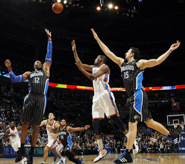 Oklahoma City's Kevin Durant (35) takes a shot between Dwight Howard (12) and Hedo Turkoglu (15) of Orlando to put the Thunder up 123-119 with 8.1 seconds left during the NBA basketball game between the Orlando Magic and Oklahoma City Thunder in Oklahoma City, Thursday, January 13, 2011. Oklahoma City won, 125-124. Photo by Nate Billings, The Oklahoman