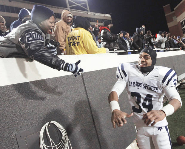 Star Spencer's Terence Olds, right, celebrates with fans after the Class 4A state championship game Saturday. Photo by Nate Billings, The Oklahoman