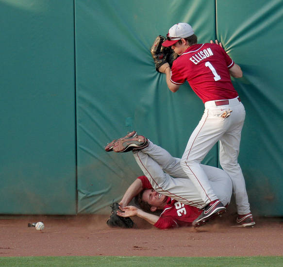 OU's Elliott Blair, left, and Christopher Ellison run into the wall in the fourth inning of the college baseball game between Oklahoma State and  Oklahoma in Stillwater, Okla., Tuesday, April 13, 2010.  Photo by Bryan Terry, The Oklahoman