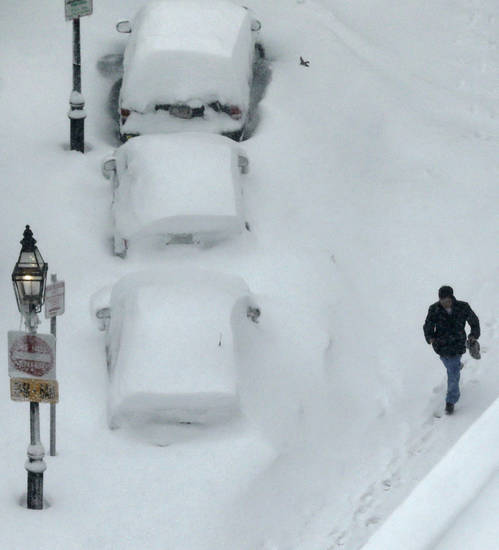 A man walks past snow covered cars in the South End neighborhood of Boston, Saturday, Feb. 9, 2013. The Boston area received about two feet of snow from a winter storm. (AP Photo/Charles Krupa)