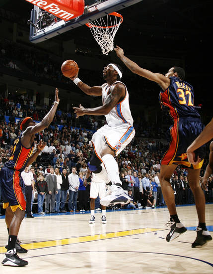 Oklahoma City's Chris Wilcox (54) tries to score between Anthony Morrow (22) and Brandan Wright (32) of Golden State Warriors during the NBA basketball game between the Golden State Warriors and the Oklahoma City Thunder at the Ford Center in Oklahoma City, Monday, December 8, 2008. BY NATE BILLINGS, THE OKLAHOMAN