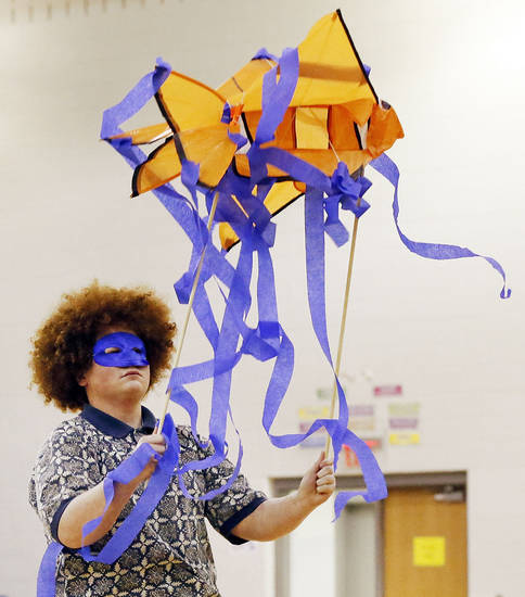 Above: Drama student Jackson Bugg, 17, dances with a paper fish during an assembly at John Marshall High School in Oklahoma City. Devon Energy gave the school its $25,000 Devon Science Giant grant during an assembly. The money will be used to build a Touch Tank interactive marine ecosystems lab.