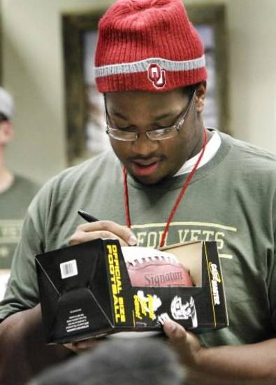 University of Oklahoma football player Adam Shead autographs a football as players visit the Veteran's Center with Quinton Carter's SOUL Foundation on Thursday, December 16, 2010, in Norman, Okla. Photo by Steve Sisney, The Oklahoman