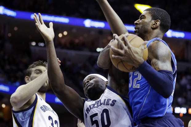 Dallas Mavericks' O.J. Mayo (32) pulls down an offensive rebound over Memphis Grizzlies' Marc Gasol (33), of Spain, and Zach Randolph (50) during the first half of an NBA basketball game in Memphis, Tenn., Friday, Dec. 21, 2012. (AP Photo/Danny Johnston)