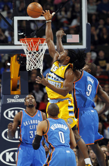 Denver Nuggets forward Kenneth Faried, top center, reaches up to tip the ball in as Oklahoma City Thunder forward Serge Ibaka (9), of the Congo, guard Russell Westbrook (0) and forward Kevin Durant, rear left, cover in the first quarter of an NBA basketball game in Denver, Sunday, Jan. 20, 2013. (AP Photo/David Zalubowski)