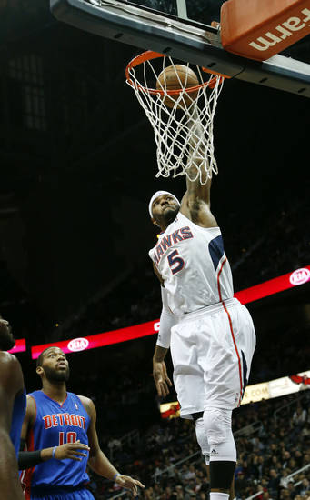 Atlanta Hawks small forward Josh Smith (5) scores as Detroit Pistons center Greg Monroe (10) looks on in the first half of an NBA basket ball game on Wednesday, Dec. 26, 2012, in Atlanta. (AP Photo/John Bazemore)