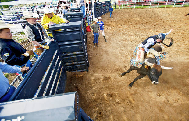 Above: Jarrod Seaton takes a ride on a bull out of the bucking chutes during the Youth Rodeo Bible Camp at the Three Crosses Arena on Wednesday in Union Valley.  Photos by Chris Landsberger, The Oklahoman