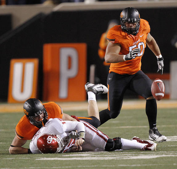 Oklahoma State's Alex Elkins (37) sacks Landry Jones (12) to cause a fumble recovered by Oklahoma State's Jamie Blatnick (50) during the Bedlam college football game between the Oklahoma State University Cowboys (OSU) and the University of Oklahoma Sooners (OU) at Boone Pickens Stadium in Stillwater, Okla., Saturday, Dec. 3, 2011. Photo by Chris Landsberger, The Oklahoman