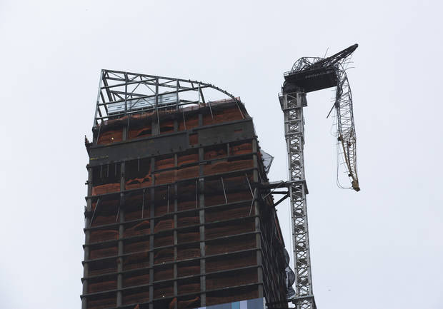 A construction crane atop a luxury high-rise dangles precariously over the streets after collapsing in high winds from Hurricane Sandy, Monday, Oct. 29, 2012, in New York. Hurricane Sandy bore down on the Eastern Seaboard&#039;s largest cities Monday, forcing the shutdown of mass transit, schools and financial markets, sending coastal residents fleeing, and threatening a dangerous mix of high winds, soaking rain and a surging wall of water up to 11 feet tall. (AP Photo/John Minchillo) ORG XMIT: NYJM110