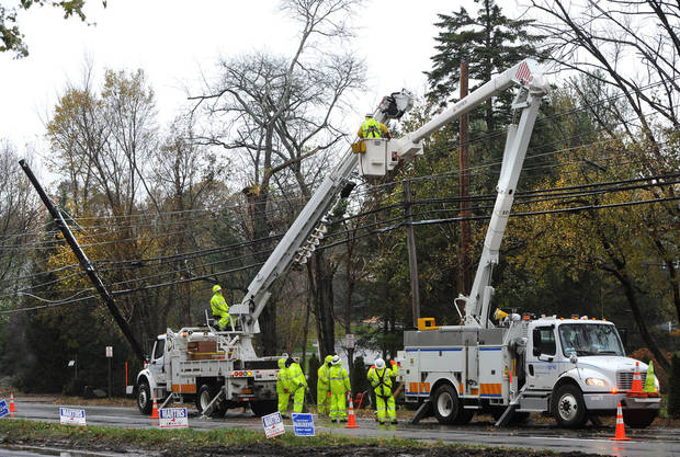 A National Grid crew from Fredonia, N.Y. , repair power lines in Port Washington, N.Y., Wednesday Nov. 7, 2012.  The lines were damaged during Superstorm Sandy.   (AP Photo/Kathy Kmonicek) ORG XMIT: NYKK104