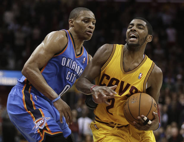 Cleveland Cavaliers' Kyrie Irving, right, drives to the basket against Oklahoma City Thunder's Russell Westbrook (0) during the fourth quarter of an NBA basketball game on Saturday, Feb. 2, 2013, in Cleveland. Irving scored a team-high 35 points for the Cavaliers' 115-110 win. (AP Photo/Tony Dejak) ORG XMIT: OHTD107