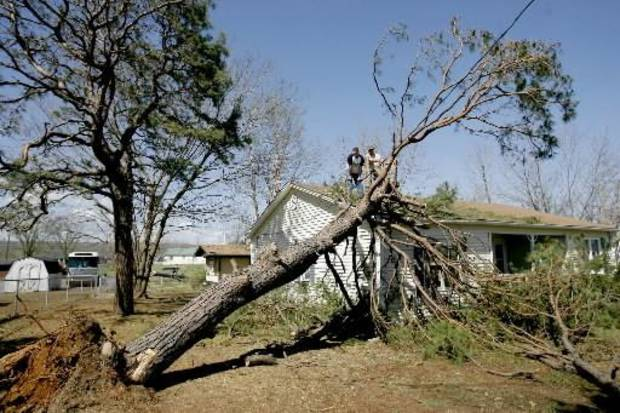 Members of the First Baptist Church of Muldrow work to clear a tree from a church parsonage in Muldrow, Okla., home, Thursday, April 10, 2008. The church parsonage was damaged Wednesday night after severe storms moved through the area. Photo by Bryan Terry