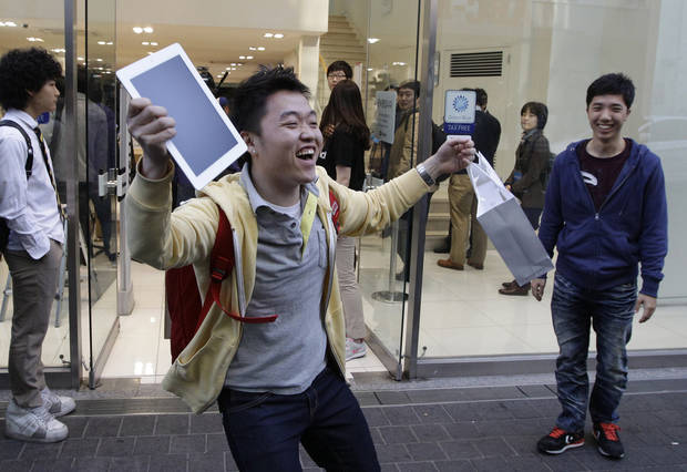 FILE - In this Friday, April 20, 2012, file photo, Baek Sung-min, 23, reacts after purchasing a new iPad at an Apple store in Seoul, South Korea.  In Google's 12th annual roundup of global trending searches, the iPad 3 was ranked fourth.  (AP Photo/Lee Jin-man)
