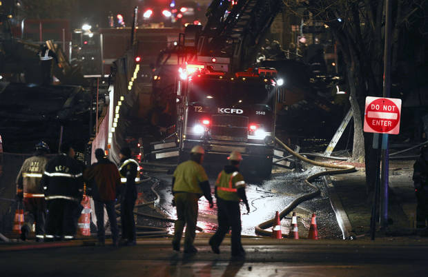 Firemen and utility workers respond to a gas explosion and massive fire Tuesday night, Feb. 19, 2013 in the Plaza shopping district in Kansas City, Mo. A car crashed into a gas main in the upscale shopping district, sparking a massive blaze that engulfed an entire block and caused multiple injuries, police said  (AP Photo/Ed Zurga)
