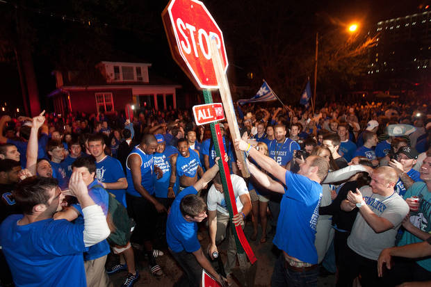 Kentucky fans uproot a traffic sign on the corner of Elizabeth and State Streets as they celebrate Kentucky's 69-61 win over Louisville in an NCAA Final Four semifinal college basketball tournament game, Saturday, March 31, 2012, in Lexington, Ky. (AP Photo/The Lexington Herald-Leader, Jonathan Palmer)