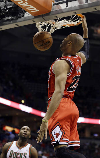 Chicago Bulls' Taj Gibson (22) dunks as Milwaukee Bucks' Luc Richard Mbah a Moute, left, watches during the first half of an NBA basketball game Wednesday, Jan. 30, 2013, in Milwaukee. (AP Photo/Jeffrey Phelps)
