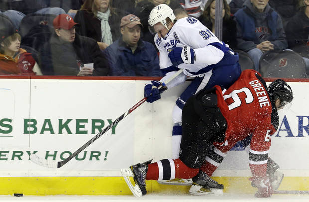 Tampa Bay Lightning center Steven Stamkos, top, is checked by New Jersey Devils defenseman Andy Greene (6) during the first period of an NHL hockey game, Thursday, Feb. 7, 2013, in Newark, N.J. (AP Photo/Julio Cortez)