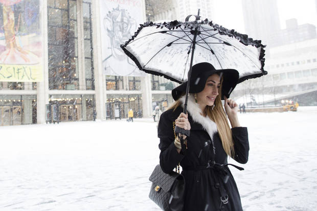 Lauren Rae Levy, of Manhattan, stands outside the Metropolitan Opera House in the snow at Lincoln Center during Fashion Week, Friday, Feb. 8, 2013, in New York. Snow began falling across the Northeast on Friday, ushering in what was predicted to be a huge, possibly historic blizzard and sending residents scurrying to stock up on food and gas up their cars. (AP Photo/John Minchillo) ORG XMIT: NYJM106