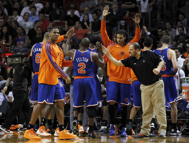 New York Knicks players give high-fives to  Raymond Felton (2) during a timeout in the final minutes of an NBA basketball game against the Miami Heat Thursday, Dec, 6, 2012, in Miami. The Knicks won 112-92. (AP Photo/Alan Diaz)