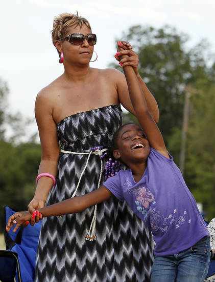 Left: Kathy McCoy, top, dances with Nelli Givens, 7, while watching Boys Night Out perform during the Arts in the City Multicultural Festival at Memorial Park in Oklahoma City on Saturday.