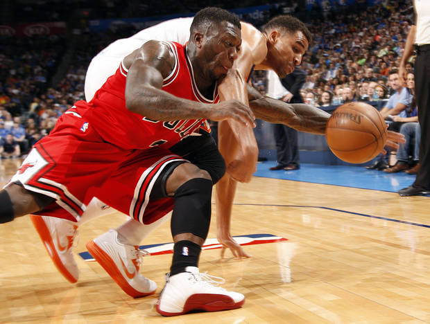 Chicago's Nate Robinson (2) and Oklahoma City's Thabo Sefolosha (2) fight for a loose ball during the NBA game between the Oklahoma City Thunder and the Chicago Bulls at Chesapeake Energy Arena in Oklahoma City, Sunday, Feb. 24, 2013. Photo by Sarah Phipps, The Oklahoman