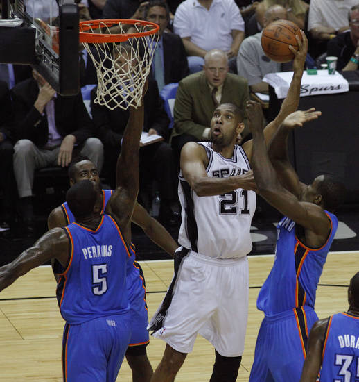 San Antonio's Tim Duncan (21) goes to the basket between Oklahoma City's Kendrick Perkins (5), James Harden (13), and Serge Ibaka (9) during Game 2 of the Western Conference Finals between the Oklahoma City Thunder and the San Antonio Spurs in the NBA playoffs at the AT&T Center in San Antonio, Texas, Tuesday, May 29, 2012. Oklahoma City lost 120-111. Photo by Bryan Terry, The Oklahoman