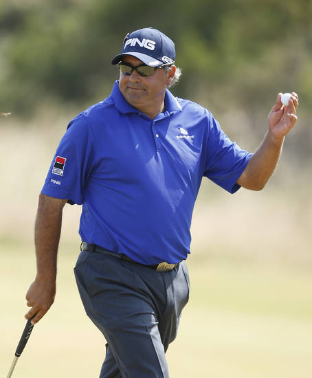 Angel Cabrera of Argentina holds up his ball after putting on the second green during the third round of the British Open Golf Championship at Muirfield, Scotland, Saturday July 20, 2013. (AP Photo/Matt Dunham)