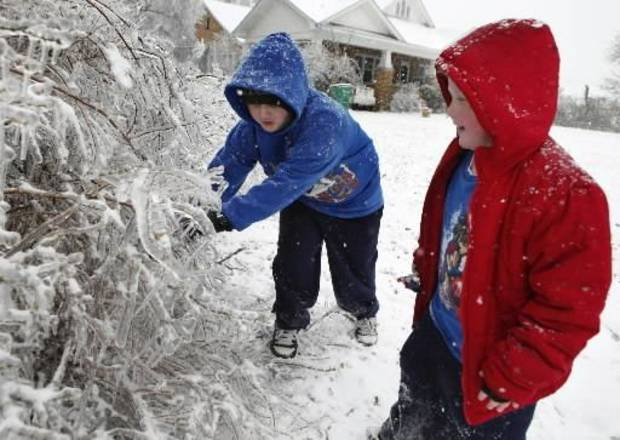 Daniel Smith, 8, and brother David, 6, break ice on limbs near their home on Friday, Jan. 29, 2010, in Purcell, Okla. after a winter storm. Photo by Steve Sisney