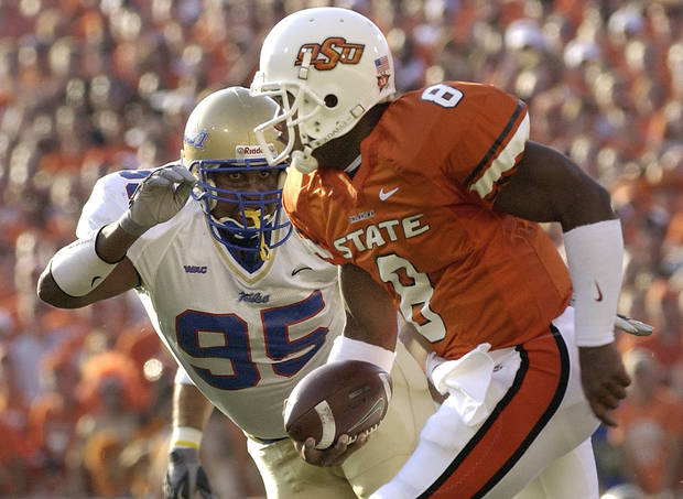 OSU's Donovan Woods runs past Tulsa's Josh Walker during the two teams' game in 2004. OSU and Tulsa have renewed their series and will play three football games and four basketball games. PHOTO BY PAUL HELLSTERN, THE OKLAHOMAN