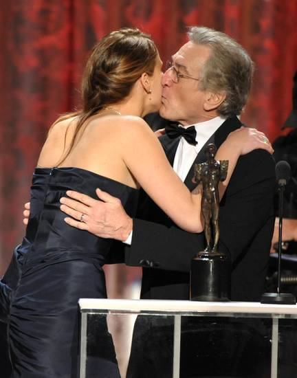 Jennifer Lawrence, left, and Robert De Niro kiss as she accepts the award for outstanding female actor in a leading role for �Silver Linings Playbook� at the 19th Annual Screen Actors Guild Awards at the Shrine Auditorium in Los Angeles on Sunday Jan. 27, 2013. (Photo by John Shearer/Invision/AP)