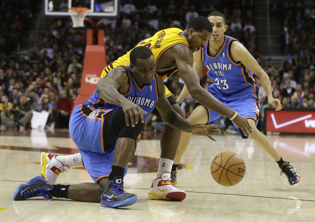 Oklahoma City Thunder's Kendrick Perkins, left, and Cleveland Cavaliers' Tristan Thompson (13) battle for a loose ball in the fourth quarter of an NBA basketball game on Saturday, Feb. 2, 2013, in Cleveland. Thunder's Kevin Martin (23) watches the play. The Cavaliers won 115-110. (AP Photo/Tony Dejak) ORG XMIT: OHTD110