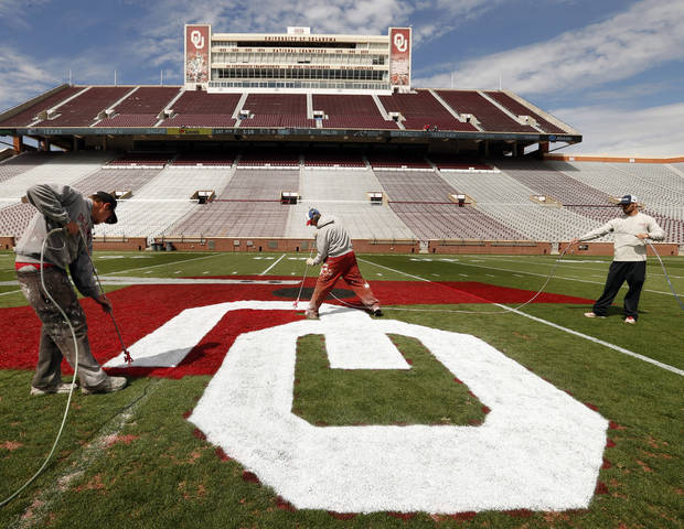 Workers paint an old style helmet on the center of Owen Field at Gaylord Family/Oklahoma Memorial Stadium in preparation for Saturday's Spring Football Game at the University of Oklahoma (OU) on Friday, April 12, 2013 in Norman. Photo by Steve Sisney, The Oklahoman