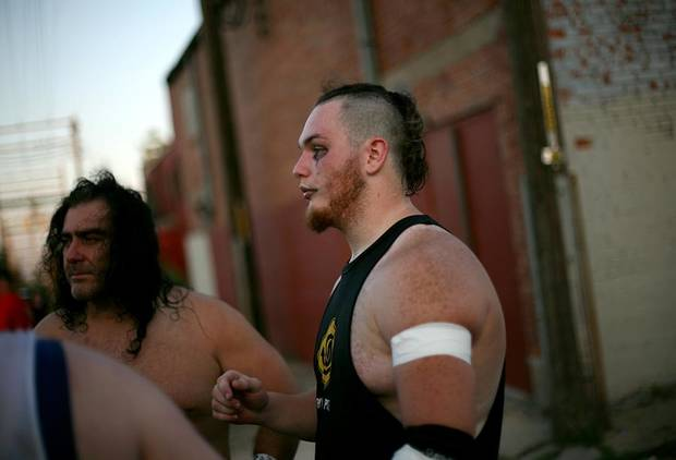 "Brandan Bulmer, who wrestles under the name ""Drake Gallows"" talks with other wreslters including Eric Torres (left) who wrestles under the name ""Rick Russo"" critque their show and plan the next match during a show by members of Sooner World Class Wrestling at the historic Yale Theater in the Capitol Hill neighborhood in south Oklahoma City on Saturday, July 23, 2011. Bulmer's brother Dallas Bulmer, who wrestled under the name Crisstopher ""The Freakshow"" Crow, died in a car accident on June 22, 2011. Saturday's show was the third of three tribute shows dedicated to Bulmer. Photo by John Clanton, The Oklahoman"