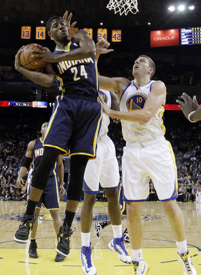 Indiana Pacers' Paul George (24) grabs a rebound next to Golden State Warriors' David Lee (10) during the first half of an NBA basketball game in Oakland, Calif., Saturday, Dec. 1, 2012. (AP Photo/Marcio Jose Sanchez)