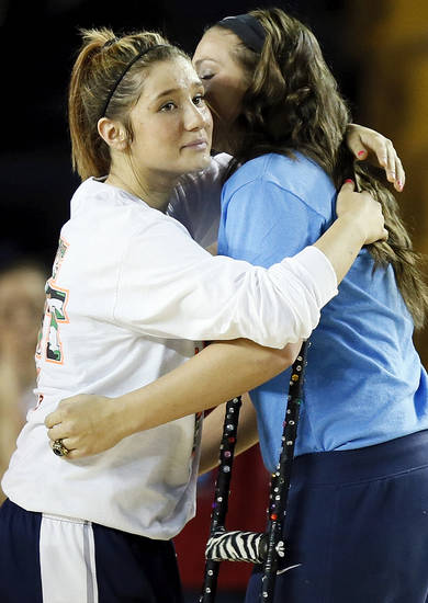 Shawnee's Bailey Taylor, left, hugs injured teammate McKenzie Cooper during introductions before the Class 5A girls championship high school basketball game in the state tournament at the Mabee Center in Tulsa, Okla., Saturday, March 9, 2013. Taylor wore Coopers' number, 20, in the semifinal and championship games to honor her. Photo by Nate Billings, The Oklahoman