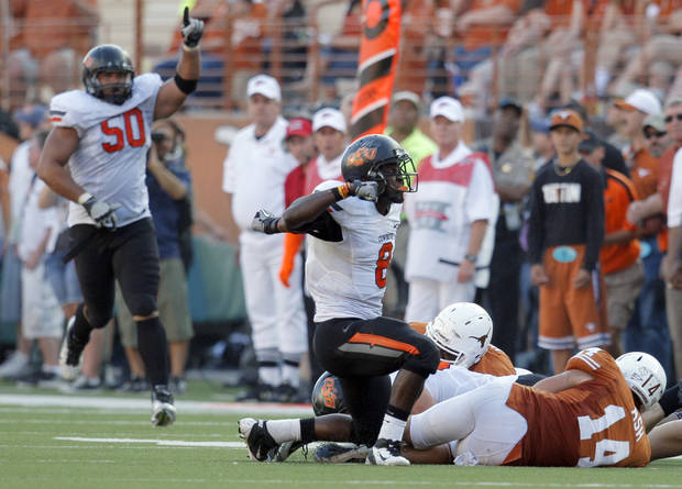 Oklahoma State's Daytawion Lowe (8) celebrates a fumble recovery as Texas' David Ash (14) lies on the ground during second half of a college football game between the Oklahoma State University Cowboys (OSU) and the University of Texas Longhorns (UT) at Darrell K Royal-Texas Memorial Stadium in Austin, Texas, Saturday, Oct. 15, 2011. Photo by Sarah Phipps, The Oklahoman