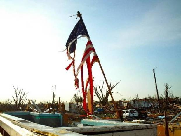 A torn American flag stands in the wreckage of a church in Joplin, Mo., Tuesday, May 24, 2011. Rescue crews worked through the rain-soaked chill of night, ignoring lightning and strong winds to dig through splintered homes, crumpled businesses and crushed cars in Joplin. (AP Photo/Robert Ray)
