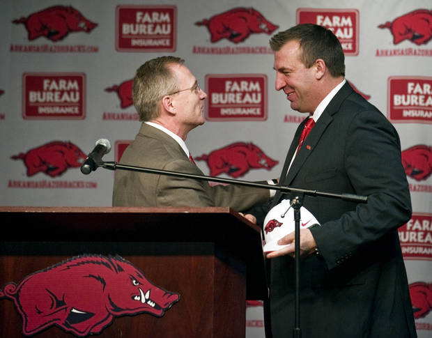 Arkansas athletic director Jeff Long, left, presents new Arkansas football coach Bret Bielema, right, with an Arkansas cap, during a news conference to announce Bielema's hire in Fayetteville, Ark., Wednesday, Dec 5, 2012. Bielema, who will be paid $3.2 million annually for six years, replaces interim coach John L. Smith, who was hired after Bobby Petrino was fired in April. (AP Photo/April L. Brown)