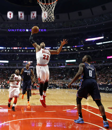 Chicago Bulls' Taj Gibson (22) goes up for a dunk as Nate Robinson (2) and Charlotte Bobcats' Brendan Haywood (33) and Ben Gordon watch during the first half of an NBA basketball game, Monday, Jan. 28, 2013, in Chicago. (AP Photo/Charles Rex Arbogast)
