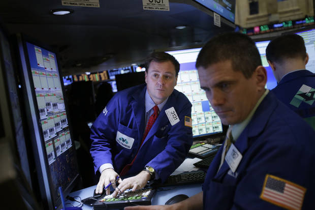 Traders work on the floor at the New York Stock Exchange in New York, Wednesday, Jan. 2, 2013. The �fiscal cliff� compromise, for all its chaos and controversy, was enough to send the stock market shooting higher Wednesday, the first trading day of the new year. (AP Photo/Seth Wenig)