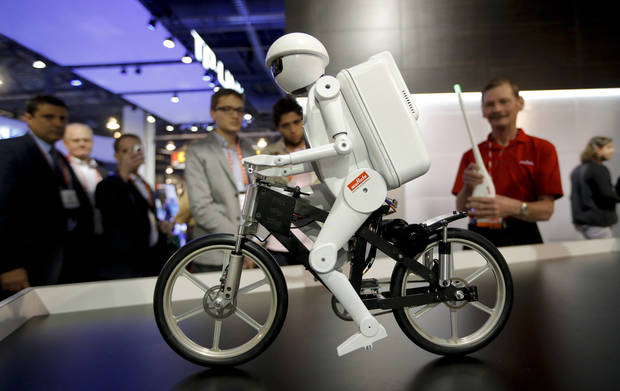 Murata Boy, a bicycle riding robot, rides a bike at the Murata booth at the at the International Consumer Electronics Show in Las Vegas, Tuesday, Jan. 8, 2013. (AP Photo/Jae C. Hong)