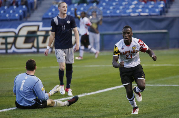 Maryland's Schillo Tshuma (23) reacts after scoring a goal in the first half of a NCAA College Cup men's championship semifinal soccer match at Regions Park, Friday, Dec. 7, 2012, in Hoover, Ala. At left is Georgetown's Tomas Gomez (1) and Cole Seiler (14). (AP Photo/Dave Martin)