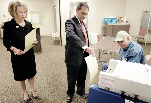 Randy Brogdon places his ballot in the ballot box as his wife Donna waits her turn after voting in the Oklahoma primary election at Faith Lutheran Church in Owasso  July 27, 2010. Looking on is inspector Wayne Harvey. MIKE SIMONS/Tulsa World
