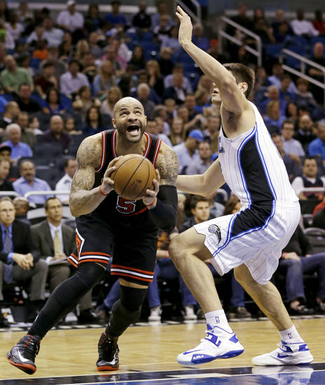 Chicago Bulls forward Carlos Boozer, left, makes a move to the basket past Orlando Magic forward Nikola Vucevic, of Montenegro, during the first half of an NBA basketball game, Wednesday, Jan. 2, 2013, in Orlando, Fla. (AP Photo/John Raoux)