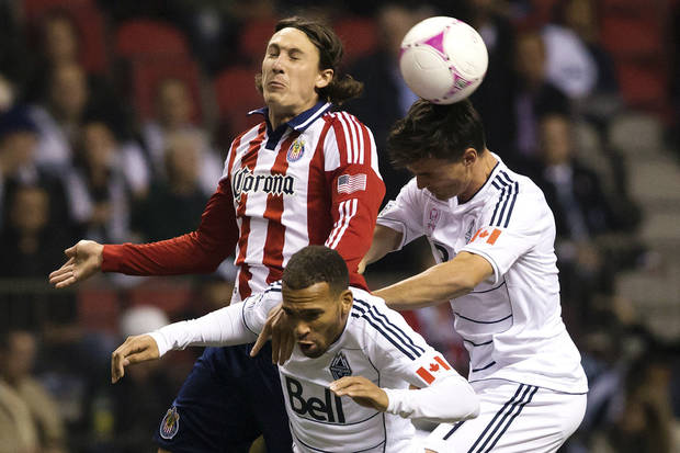Chivas USA's Ben Zemanski, left, vies for the ball with Vancouver Whitecaps' Matt Watson, center, of England, and Alain Rochat, of Switzerland, during the first half of their MLS soccer match, Wednesday, Oct. 3, 2012, in Vancouver, British Columbia. (AP Photo/The Canadian Press, Darryl Dyck)