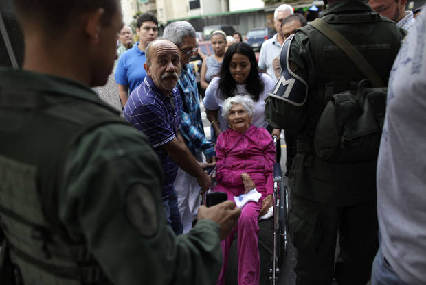 An elderly woman in a wheel chair is helped to enter a polling station during the presidential election in Caracas, Venezuela, Sunday, Oct. 7, 2012. President Hugo Chavez is running against opposition candidate Henrique Capriles. (AP Photo/Ramon Espinosa)