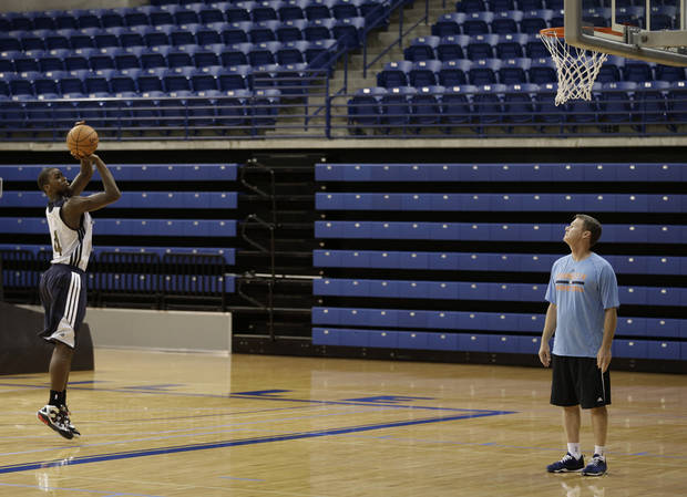Charlotte Bobcats assistant coach Mark Price, right, looks on as Michael Kidd-Gilchrist, left, takes a shot during practice at NBA basketball training camp in Asheville, N.C., Tuesday, Oct. 1, 2013. (AP Photo/Chuck Burton)