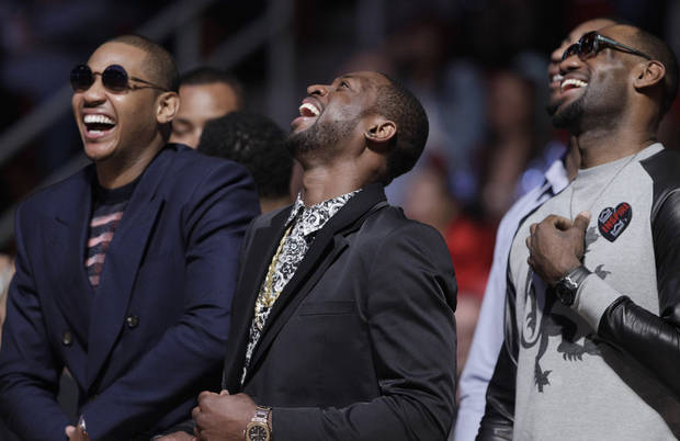 Carmelo Anthony of the New York Knicks, left,  joins Dwyane Wade and LeBron James of the Miami Heat watch a replay at the dunk contest during NBA All-Star Saturday Night basketball in Houston on Saturday, Feb. 16, 2013. (AP Photo/Eric Gay)